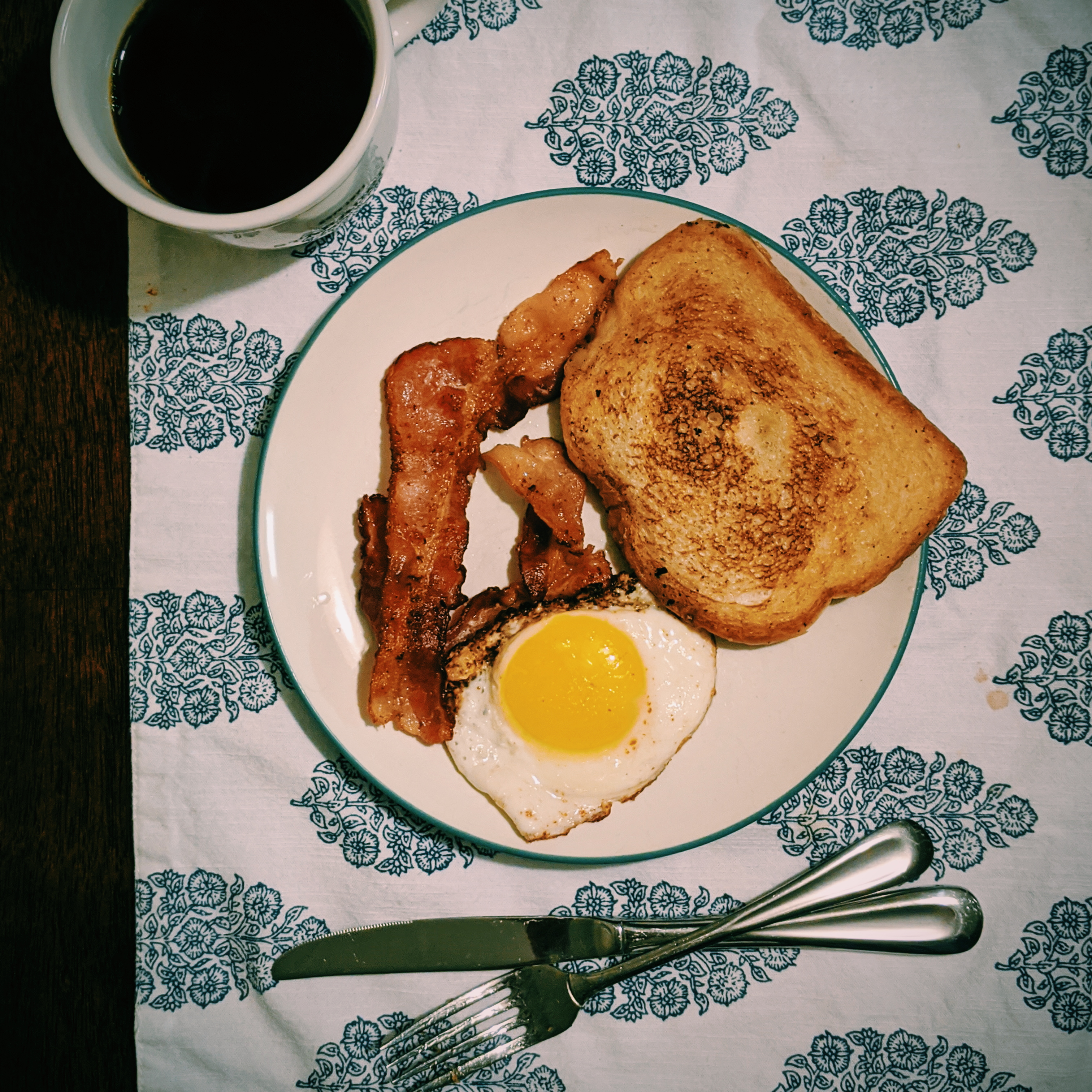 Bacon, egg, and fried bread with a black coffee