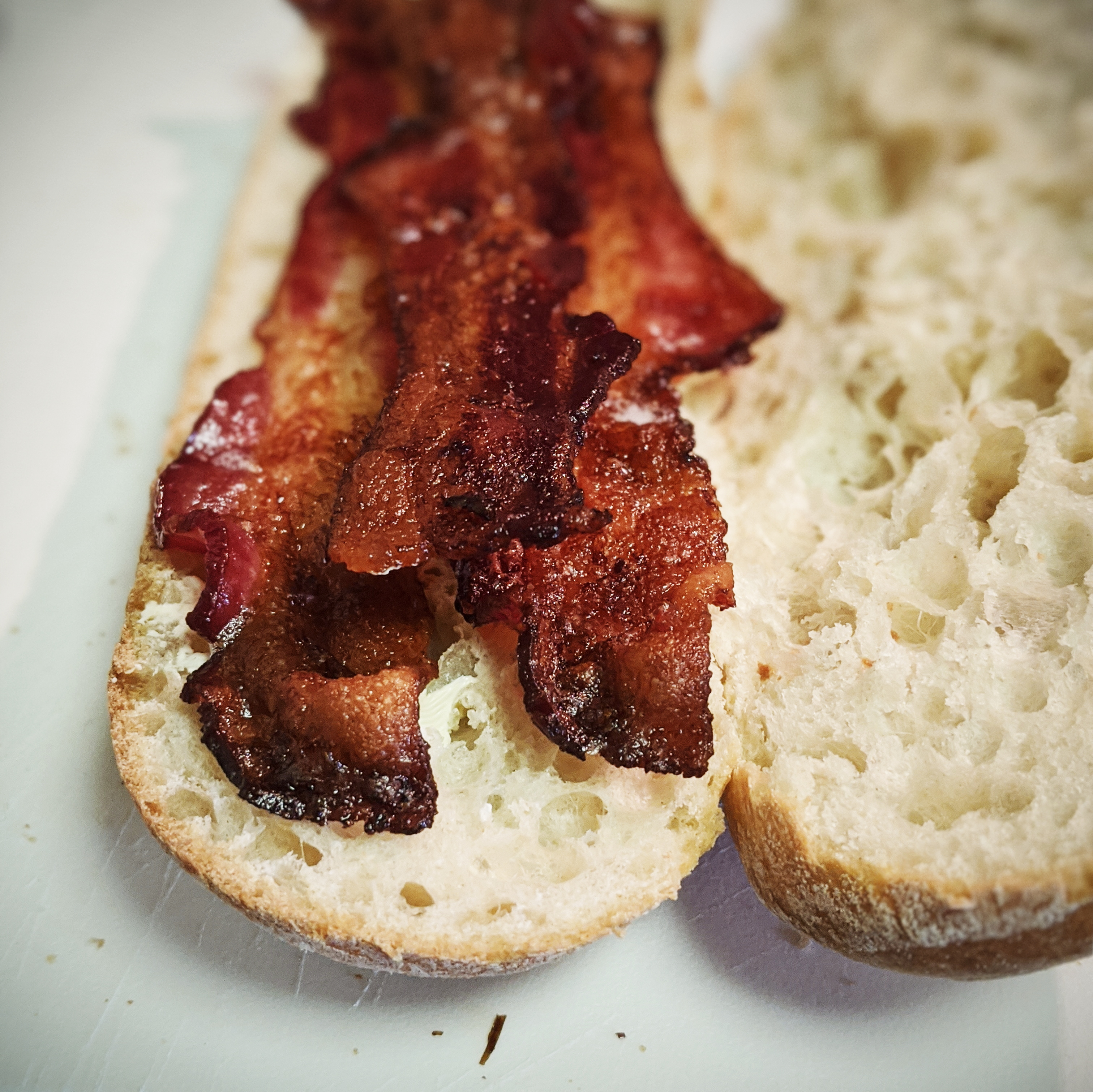 close up of cooked bacon on a baguette