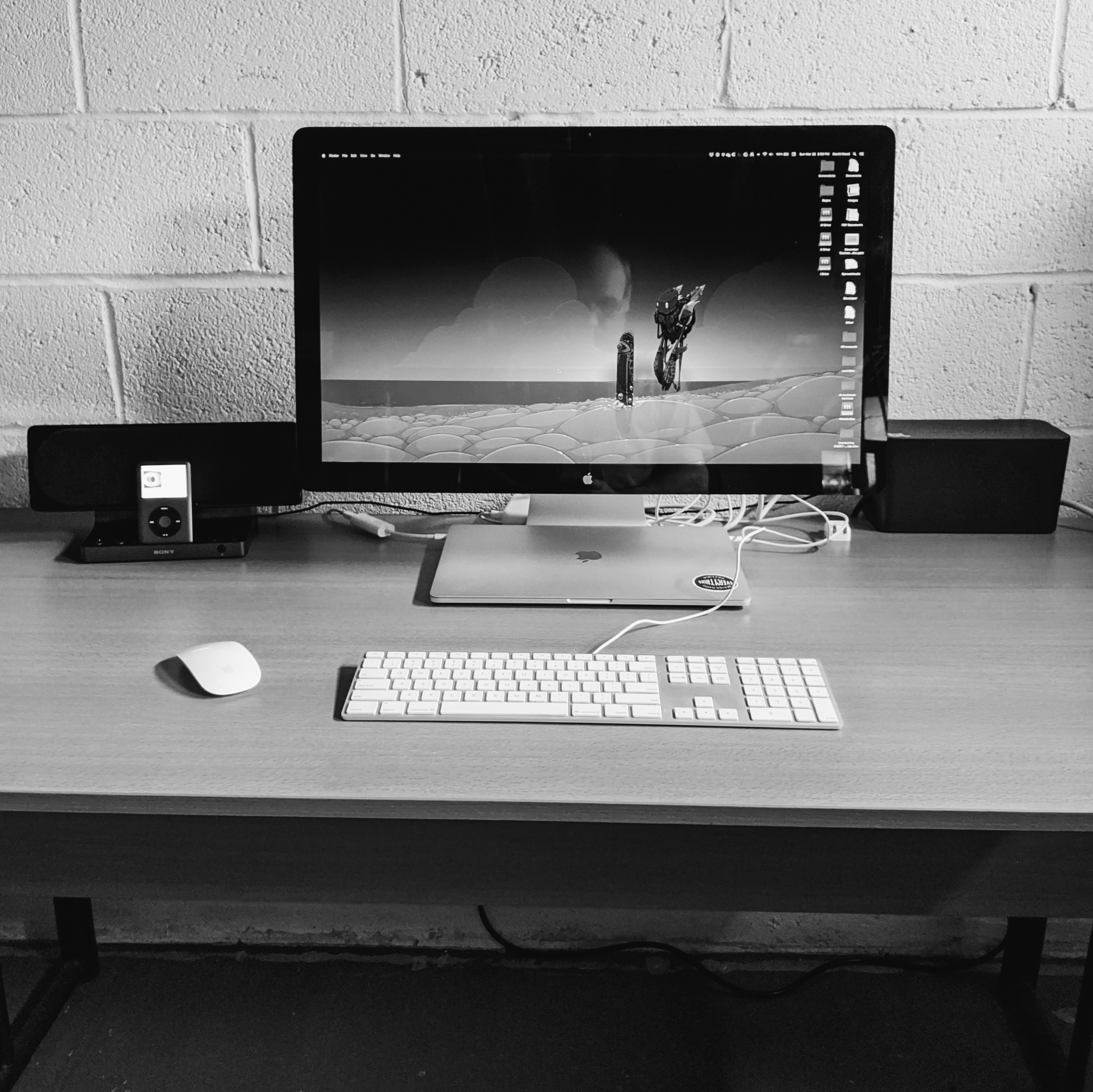 Black and white photo of desk and computer in basement