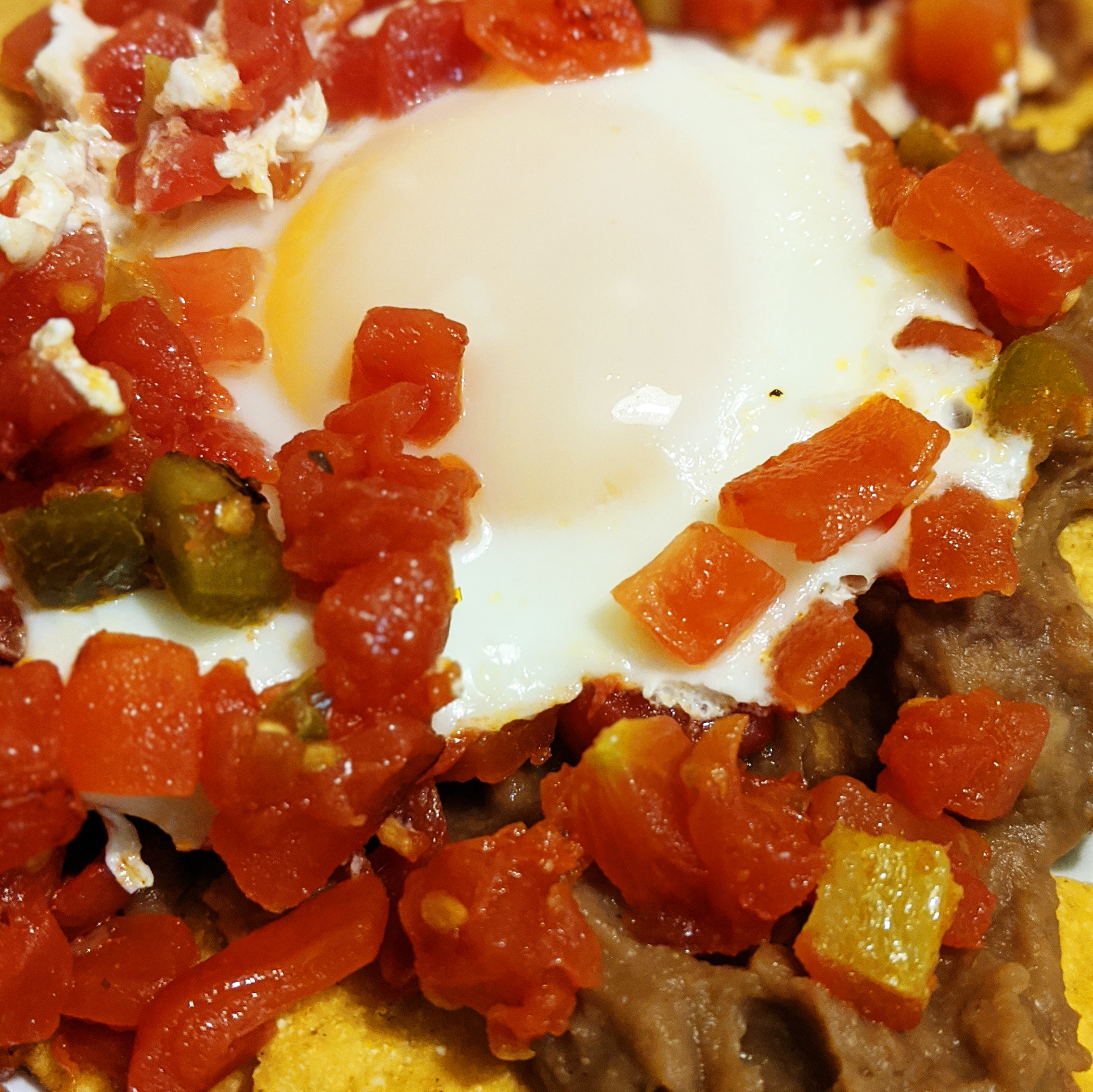 fried egg with tomatoes and chilis on top of refried beans and tostados